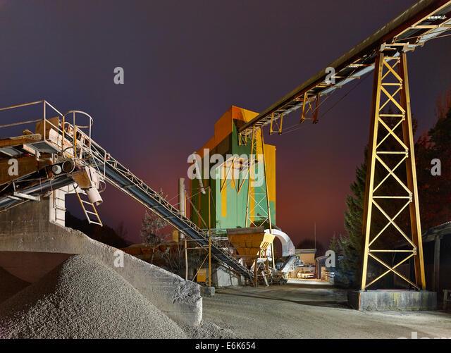 Conveyor belt in a gravel plant, production of tarmac, at dusk, Wörgl, Tyrol, Austria - Stock Image