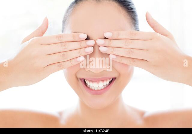 MODEL RELEASED. Young Asian woman with hands touching covering eyes, portrait. - Stock-Bilder