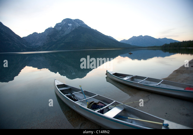 Two canoes at dusk are beached on the shore of Lake Leigh with the Grand Tetons in the distance. - Stock Image
