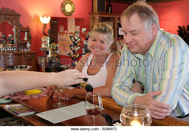 Michigan Traverse City Leelanau Peninsula Gill's Pier vineyard winery tasting room bar pour wine man woman couple - Stock Image