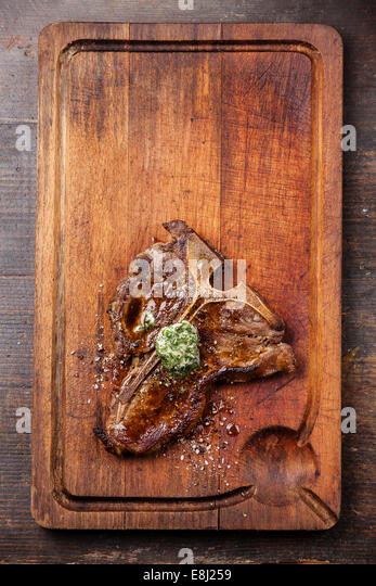 Grilled T-Bone Steak and herbs butter on meat cutting board - Stock Image