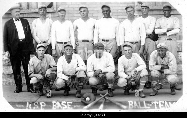 Portrait of the Nebraska State Penitentiary baseball team in uniform, with three bats, a glove, and a ball positioned - Stock Image