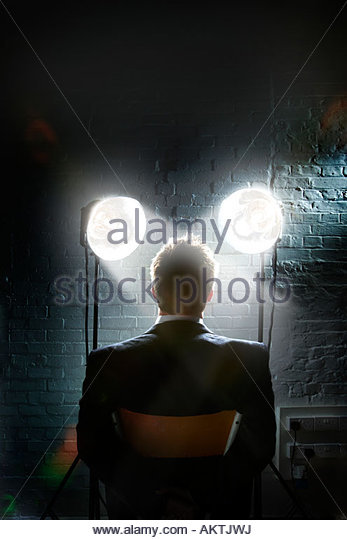 Interrogation scene with spotlights shining in a man's face - back view of restrained businessman - Stock Image
