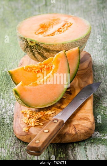 Cantaloupe melon slices on olive wood cutting board - Stock Image