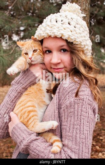 teenager holding cat - Stock Image