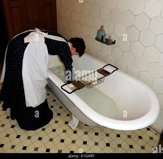 Victorian bath with butler pouring hot water in a tiled en-suite bathroom.  Decorated to 19th century requirements, - Stock Image