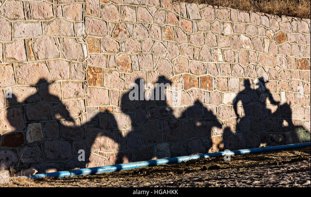 Silao, Mexico. 06th Jan, 2017. Mexican cowboys cast shadows along a wall as they ride to the top of Cubilete Mountain - Stock Image