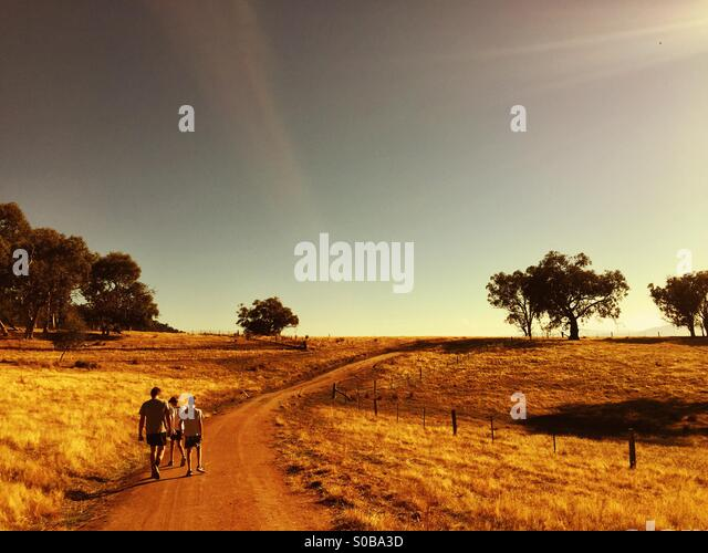 A father and two sons walk along a track in the country in Australia - Stock Image