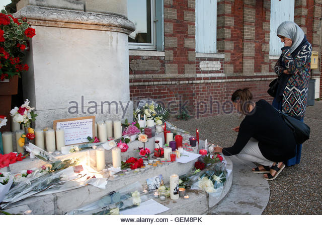 Women gather near flowers and candles at the town hall in Saint-Etienne-du-Rouvray, near Rouen in Normandy, France, - Stock-Bilder