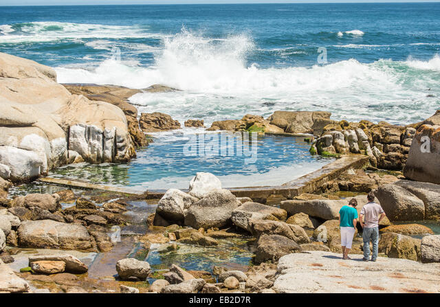 Two people standing on the rocks at Sea Point, Cape Town, near a man made tidal pool, watching the waves crashing - Stock Image