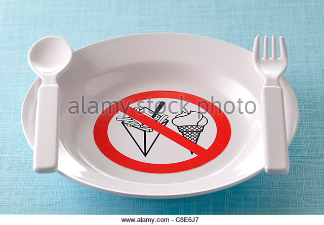 Plate decorated with a sign forbidding fat and sweet food - Stock Image
