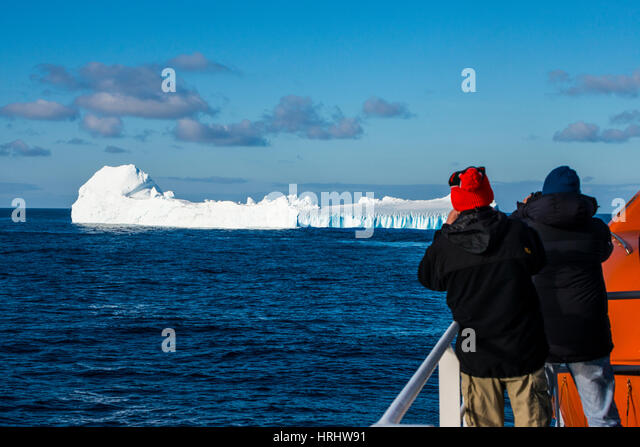 Tourists watching an iceberg floating in the South Orkney Islands, Antarctica, Polar Regions - Stock Image