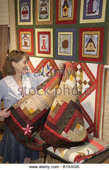 Arkansas Little Rock Historic Arkansas Museum gift shop woman fold quilt handcraft frontier period heritage regional - Stock Image