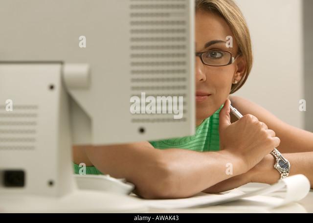 Woman looking at computer monitor - Stock Image