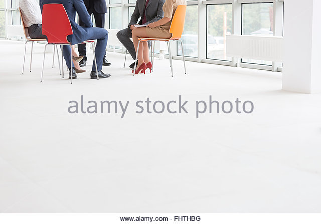 Low section of businesspeople sitting in office at the window - Stock Image