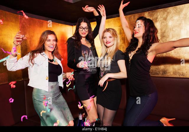 Four female friends celebrating in nightclub - Stock Image