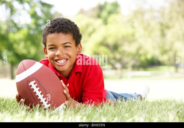 Boy In Park With American Football - Stock-Bilder