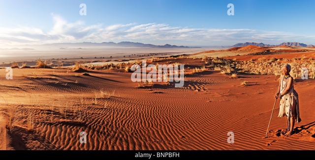 Elderly Bushman / San woman standing in desert - Stock Image
