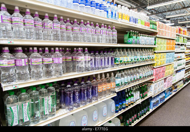 A natural foods grocery store aisle with shelves of bottled water. - Stock Image