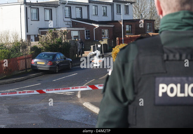 Armagh, Northern Ireland. 15th March 2013. Police officer looks on from behind a police cordon tape as a Bomb squad - Stock Image