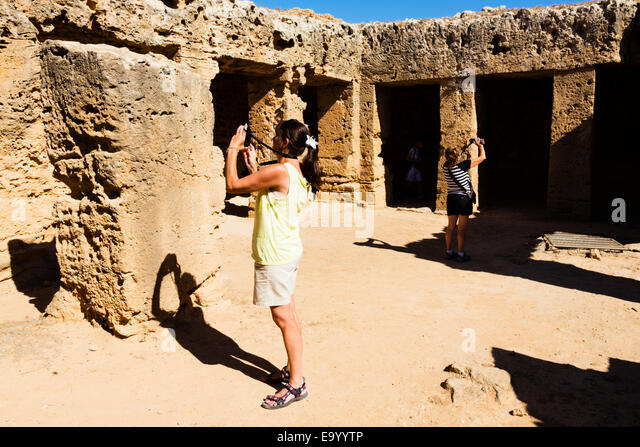 Female tourists take photos of the Tombs of the Kings, Paphos, Cyprus. - Stock Image