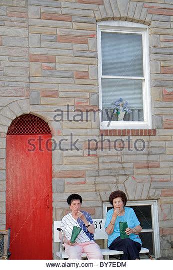 Baltimore Maryland Little Italy ethnic neighborhood working class community row house woman neighbor sitting bench - Stock Image