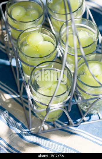 Glasses of water with green grapes in a glass carrier - - Stock Image