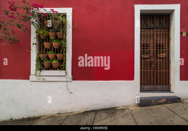 Colourful building with painted door guards and decorative planters in Old San Juan (Puerto Rico) - Stock Image