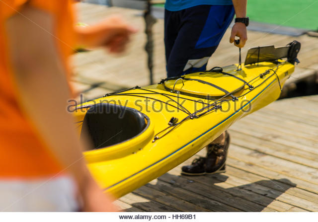 Colorful canoes and kayaks by the lake on a sunny day. Used for summer boating and recreational sport activities - Stock-Bilder