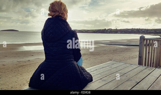 young elegant woman sitting on wood on beach - Stock-Bilder