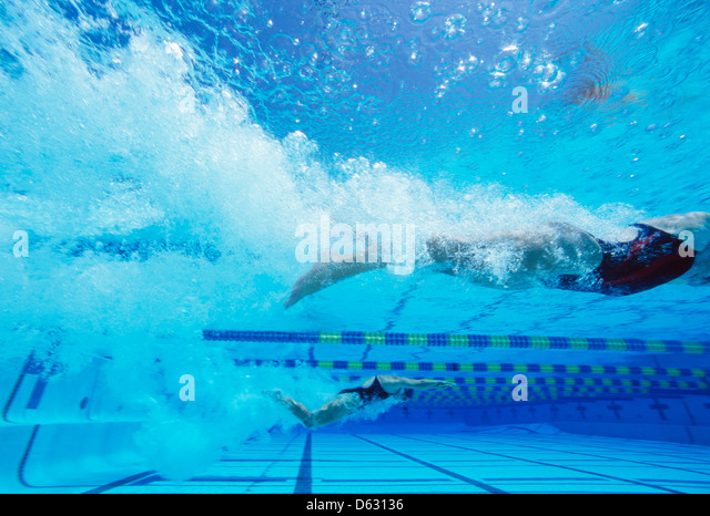 Young Caucasian female swimmers swimming in pool - Stock Image
