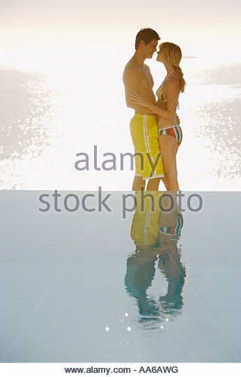 Profile of man and woman in swimsuits embracing outdoors with water - Stock-Bilder