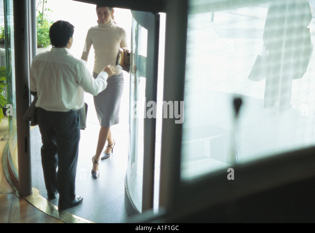 Man standing in doorway as woman enters - Stock Image