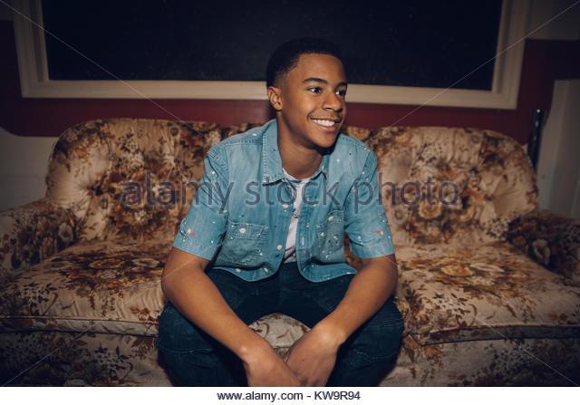 Smiling,confident African American tween boy sitting on sofa,looking away - Stock Image