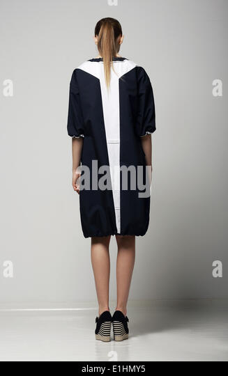 Rear View of of Trendy Chichi Woman in White-Black Contrast Raincoat. Vogue - Stock Image