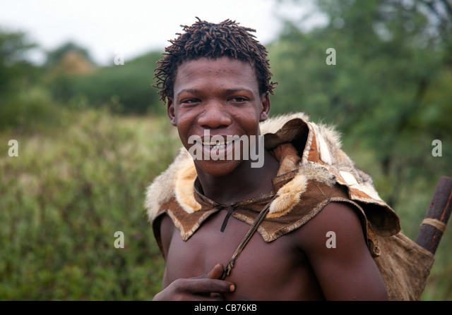 Bushman dressed in animal skin in the Kalahari desert near Ghanzi, Botswana, Africa - Stock Image