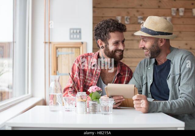 Gay couple sat viewing menu in cafe - Stock-Bilder