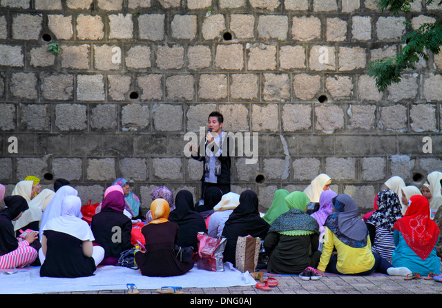 Hong Kong China Kowloon Tsim Sha Tsui Kowloon Park Muslim Asian woman meeting man speaking microphone - Stock Image