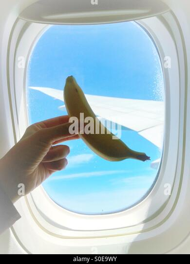 Banana in the sky. Airplane window with wing and blue sky in background and in foreground hand holding banana served - Stock Image