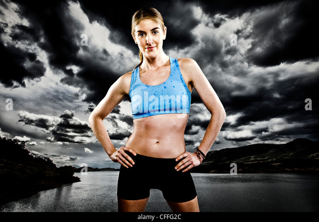 An athletic woman poses while running with a blue sports bra and black running shorts in front of Horsetooth Reservoir. - Stock Image