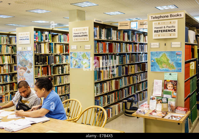 Hawaii Hawaiian Honolulu Hawaii State Library book shelves Black man woman couple - Stock Image