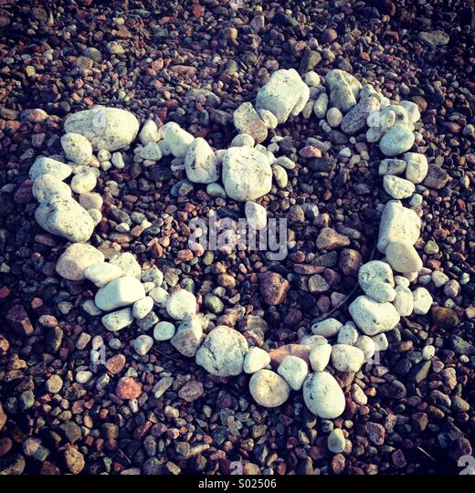 A heart made of white stones and pebbles on a colourful beach - Stock-Bilder