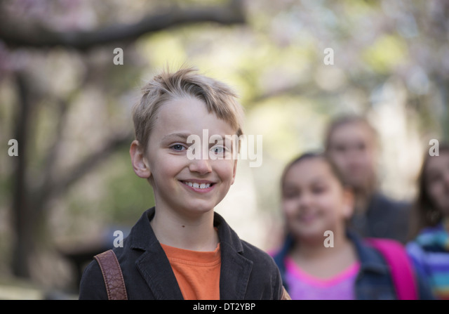 A group of children on the sidewalk carrying bags - Stock Image