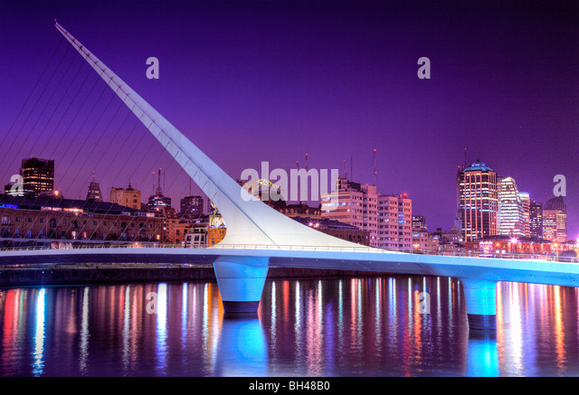 Bridge of the Woman view at dusk, with city silhouette at background and water reflections. Puerto Madero, Buenos - Stock-Bilder