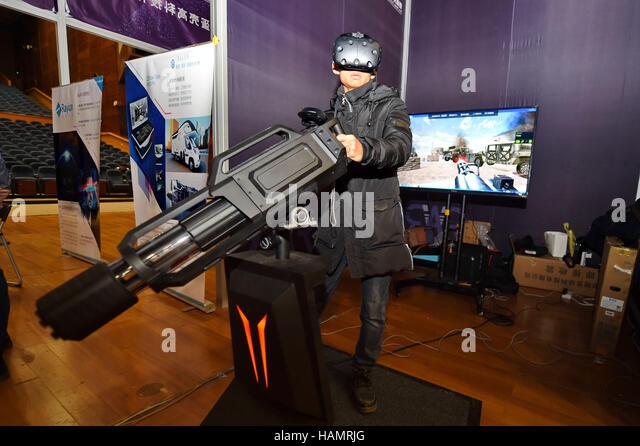 Changchun, China's Liaoning Province. 2nd Dec, 2016. A citizen tries a VR shooting game during a VR/AR expo - Stock Image