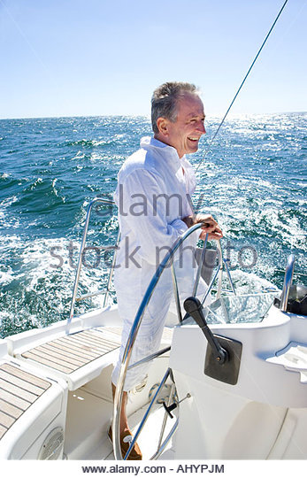 Mature man standing at helm of yacht out at sea, steering, smiling, side view - Stock Image