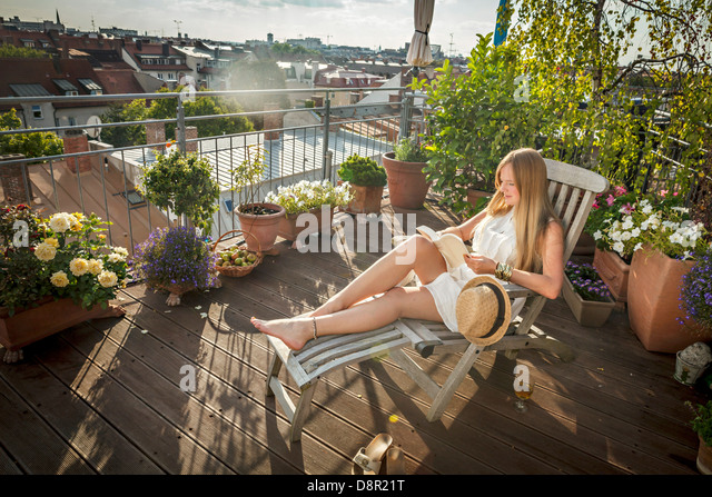 Woman sunbathing on city balcony stock photos woman for Balcony sunbathing