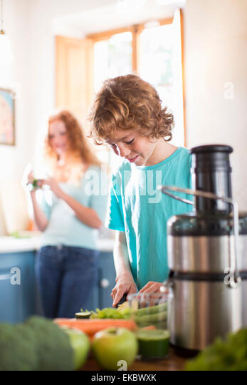 Teenage boy cutting vegetables in kitchen - Stock Image