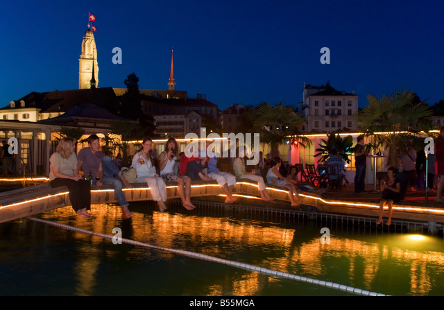Switzerland Zurich bare foot bar at river Limmat at night background Grossmunster - Stock Image