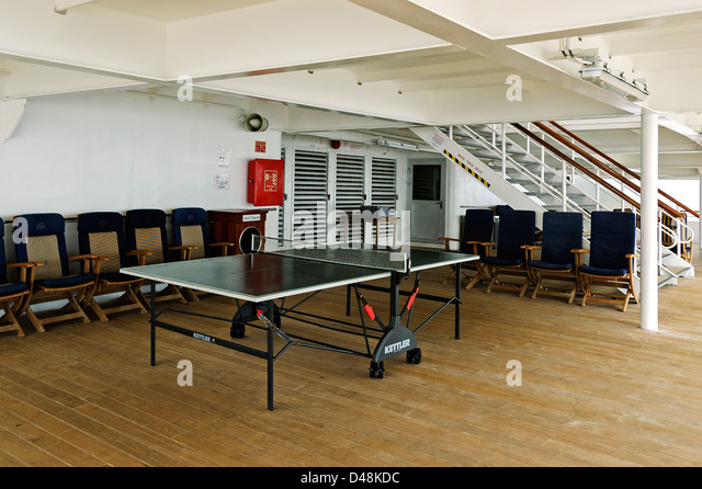 Comfortable chairs are placed around a fairly open table tennis table partially protected by the floor of the deck - Stock Image
